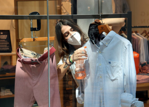 A staff member disinfects a shirt on display in a clothes shop in Diagonal Mar shopping center (by Marta Casado Pla)