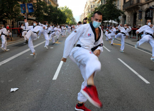 A group of people perform martial arts during a sports demonstration in the middle of Barcelona (by Miquel Codolar)