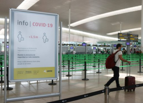 Traveller walks past a Covid-19 sign in the Barcelona airport (by Norma Vidal)