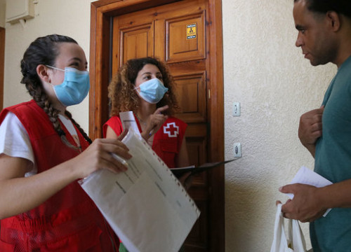Red Cross volunteers deliver educational material to a family (by Gemma Sánchez)