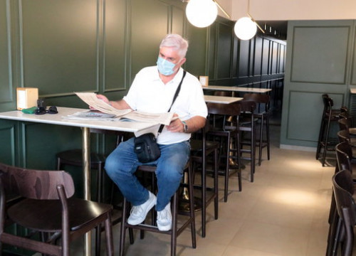 A customer reads a newspaper in a restaurant in Lleida on the first day the interiors were allowed to reopen, August 11, 2020 (by Salvador Miret)