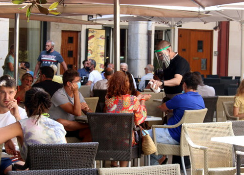 Image of a waiter serving sanitizer to clients in a bar terrace, in Girona, on August 17, 2020 (by Xavier Pi)
