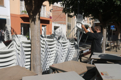 A bar owner in northern Catalonia stacks chairs and gathers terrace tables together when Covid-19 restrictions were implemented preventing bars from opening on October 16, 2020 (by Xavier Pi)