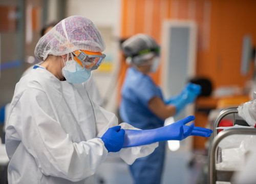 A staff member in Barcelona's Hospital Clínic ICU puts on protective gloves (Francisco Àvia/Hospital Clínic)