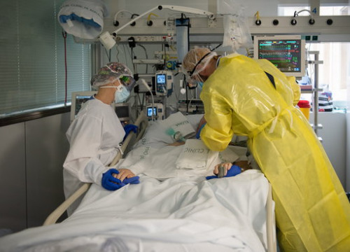 Two health workers visiting a Covid-19 patient in an ICU in Barcelona's Hospital Clínic hospital on October 23, 2020 (by Hospital Clínic)