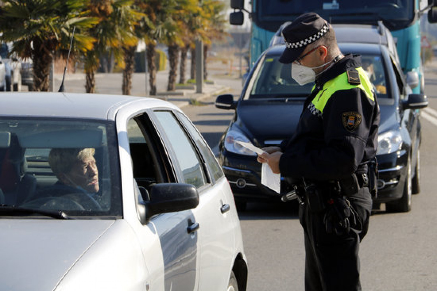 A police officer stopping a driver in Mollerussa to enforce Covid mobility restrictions (by Oriol Bosch)