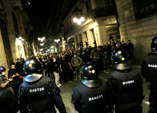 Anti-restrictions protesters in front of Catalan police officers (by Laura Fíguls)