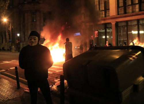 A trash can being burned down as a protesters wears an Anonymous group mask, on October 30, 2020 (by Laura Fíguls)