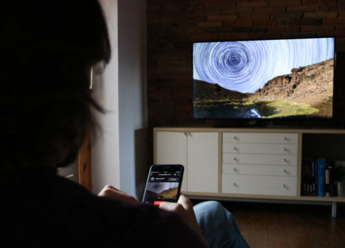 Co-founder of WindowSight, Pol Rosset, browses art through his phone and displays it on a television (by Albert Segura Lorrio)