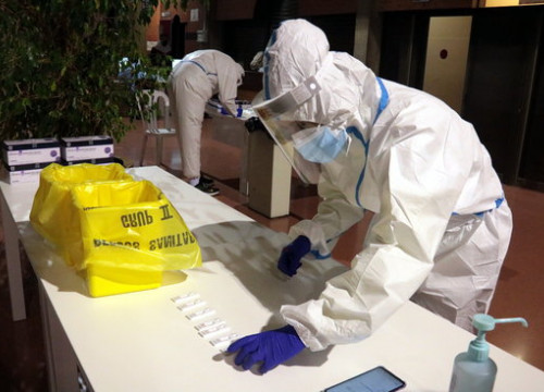 A health worker in full protective equipment deposits a sample collected by an antigen test in Lleida (by Salvador Miret)