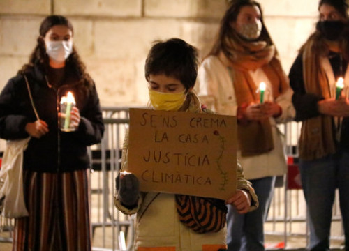 "A child holds a placard which reads ""Our house is being burnt, climate justice"" at a protest on December 11, 2020 (by Blanca Blay)"