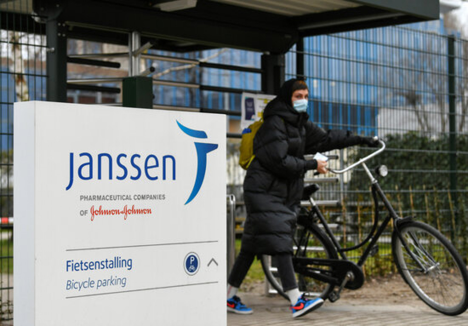 A woman walks with a bicycle outside a Janssen branch in the Netherlands (by REUTERS / Piroschka van de Wouw)