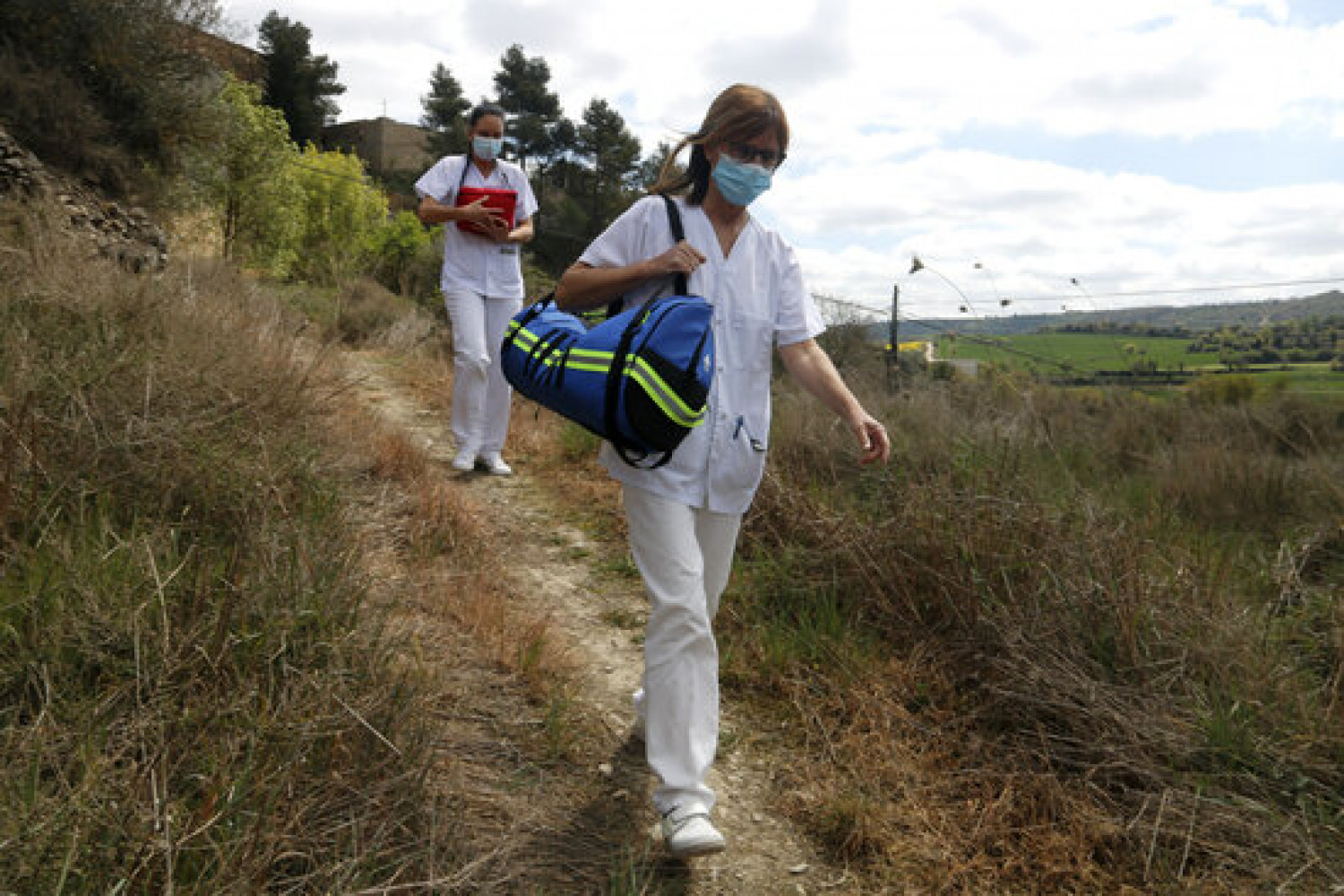 Health professionals walking on a rural pathway delivering vaccines to the village of Ivorra in central Catalonia (by Oriol Bosch)
