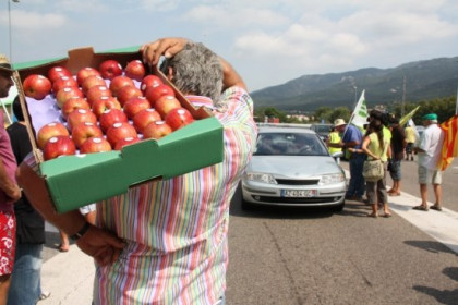 A farmer carrying a box of apples to be distributed to drivers coming from France (by T. Tapia)