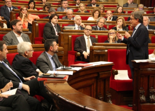The Catalan President, Artur Mas (standing up), addressing the ERC's leader, Oriol Junqueras, at the Catalan Parliament on Wednesday (by R. Garrido)
