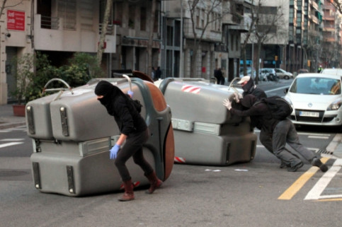 Two garbage containers are moved to block on city centre street and afterwards they are burnt (by A. Salamé)