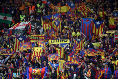 "Barcelona fan holds up a ""Llibertat"" (freedom) banner before the match as Catalan and Catalan independence flags are displayed (courtesy of REUTERS/Susana Vera)"