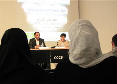 Two attendees listen to Montserrat Coll and Mohammed Halhoul at the III Young Muslims Meeting