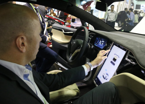 Visitor at 'Automobile Barcelona' testing the connectivity of a Tesla's prototype (by ACN)