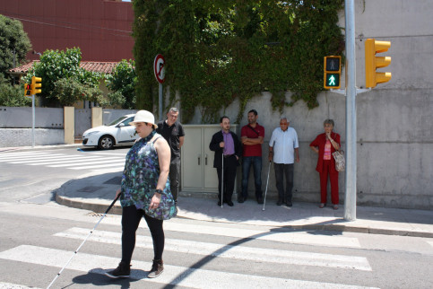 Blind woman crossing a pedestrian crossing regulated by an adapted traffic light (by ACN)