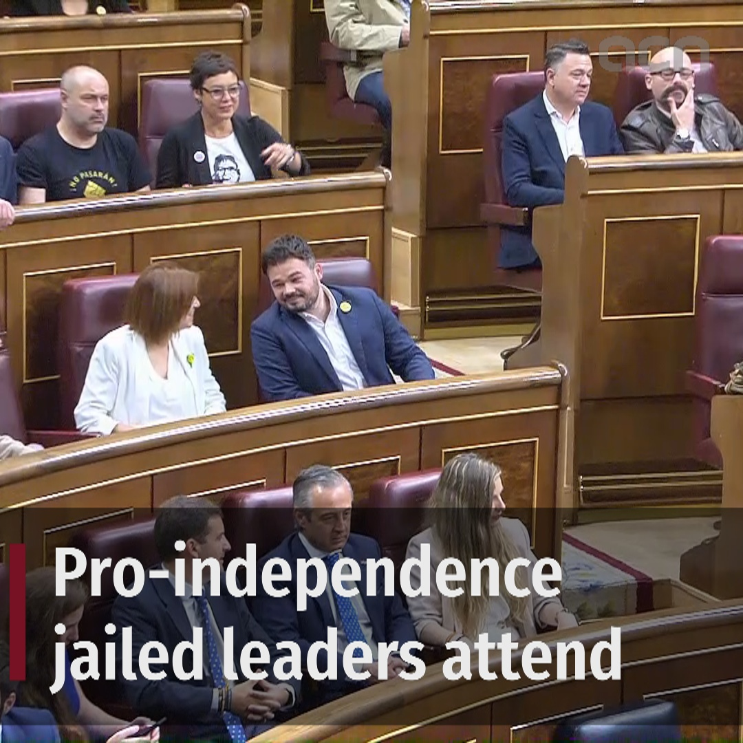 Jailed Catalan leaders are received with applause by some at Parliament's opening session