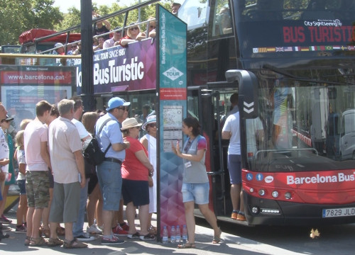 Tourists waiting in line at the tour bus stop