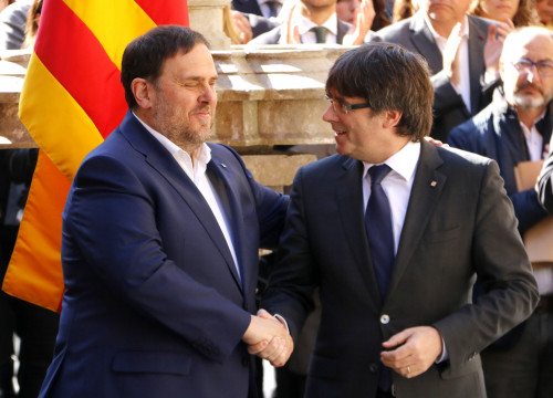 Catalan President, Carles Puigdemont shaking hands with Catalan VP, Oriol Junqueras during the event to emphasize the Government's commitment to call a referendum (by ACN)