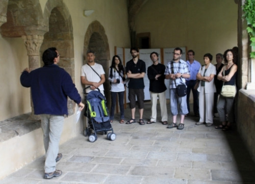 Tourists listening to a guide's explanations at the cloister of the Sant Joan de les Abadesses' Monastry, in the Pyrenees