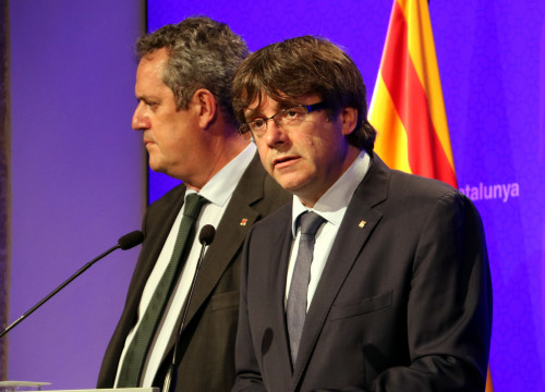 The Catalan president, Carles Puigdemont, speaking next to the home affairs minister, Joaquim Forn