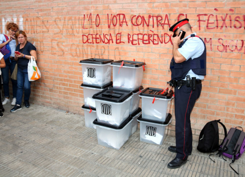 A Catalan police officer looking over some ballot boxes in Lleida (by Salvador Miret)