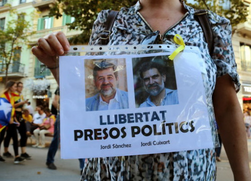 A protester holds up a printed sign calling for the release from prison of Jordi Sànchez and Jordi Cuixart (by Júlia Pérez)