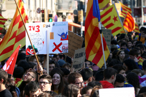 Students march in the center of Barcelona holding a sign defending one of Catalonia's public media outlets, TV3 (by ACN)