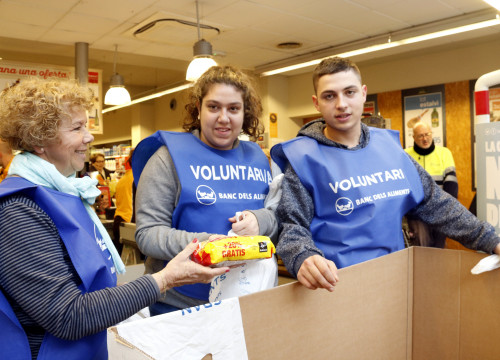 Three volunteers from the food bank for the Gran Recapte at the Marina market supermarket, on December 1 2017 (by Laura Fíguls)