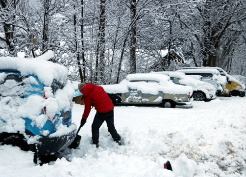 A man removing snow from his car in the Catalan Pyrenees (by Marta Lluvich)