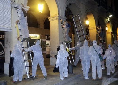 A group in white protective clothes removing yellow signs in La Bisbal d'Empordà on August 29, 2018 (by Marina López)