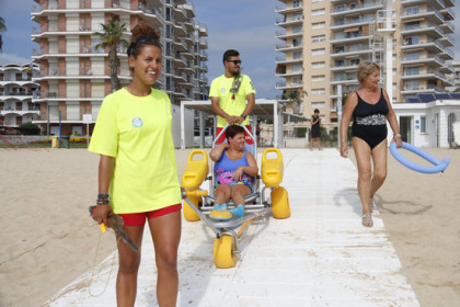 Two lifeguards help Laura Gonzàlez into the water at Torre Valentina beach (ACN)