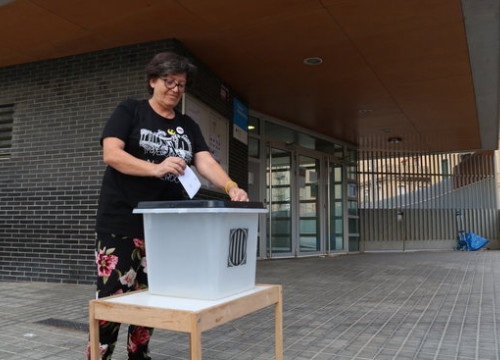 A woman symbolically casting a ballot in front of a school that was used as a polling station in the Catalan referendum (by Elisenda Rosanas)
