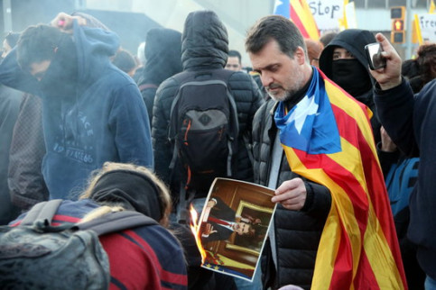 A protester wearing a Catalan independence flag burns a picture of Spain's king, Felipe VI (by Àlex Recolons)