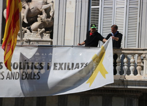 Two workers remove the banners on the balcony of the government HQ, March 22, 2019. (Photo: Miquel Codolar)