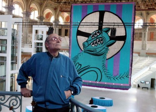 Antoni Miralda standing on a balcony in front of his 'Lamb of the Apocalypse' tapestry in the MNAC (Photo: Pau Cortina)