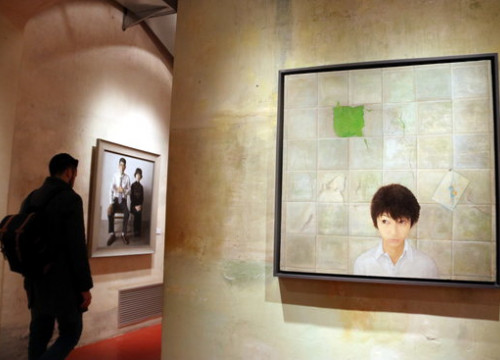 A man walking through the new Chinese realism art exhibition in the European Museum of Modern Art, Barcelona