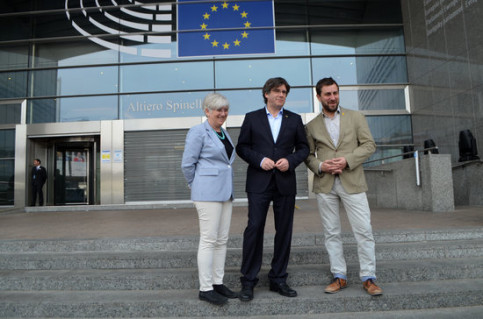 Carles Puigdemont, center, stands alongside Clara Ponsantí, left, and Toni Comín, right, at the front doors of the European Parliament. (Photo: Blanca Blay)