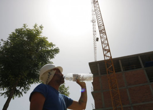 A contruction worker drinks water during the June 2019 heatwave. (Photo: Laura Cortés)
