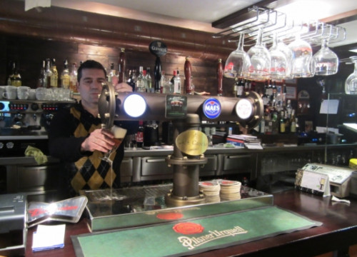 A bartender in a bar in Cerdanyola del Vallès serving a beer in 2012 (by Norma Vidal)