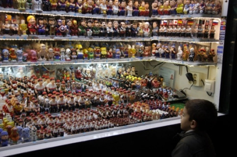 A kid looking at many Caganer figurines to sell (by ACN)