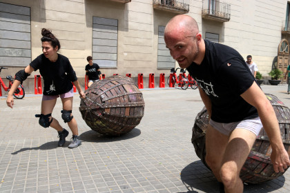 La Fura dels Baus actors drag metal eggs containing other actors near Barcelona's Maritime Museum on July 9, 2019 (Pau Cortina/ACN)