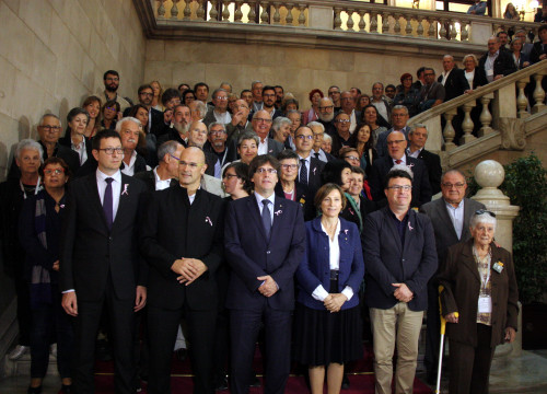 Family picture of the victims of Francoism with the Catalan President, Carles Puigdemont; the President of the Catalan Parliament, Carme Forcadell, and the Catalan Ministers Mundó and Romeva (by ANC).